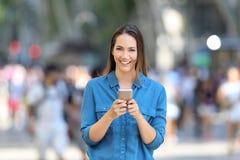 La mujer que sostiene el teléfono elegante mira la cámara Fotografía de archivo