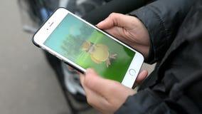 La mujer que sostiene el teléfono y que juega Pokemon va almacen de video