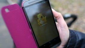 La mujer que sostiene el teléfono y que juega Pokemon va metrajes