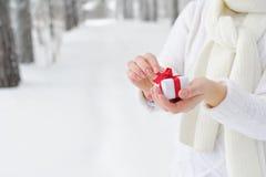 La mujer que sostiene un regalo y comienza a abrirlo Fotos de archivo libres de regalías