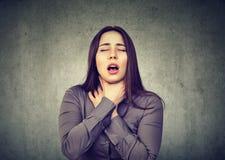 La mujer que tiene ataque de asma o que obstruye puede respiración del ` t que sufre de problemas de la respiración foto de archivo