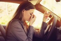 La mujer que tiene dolor de cabeza que saca los vidrios tiene que hacer una parada después de conducir el coche en atasco imagenes de archivo