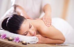 La mujer que tiene una salud detrás da masajes Imagenes de archivo