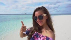 La mujer que toma el selfie y la demostración manosean con los dedos encima del océano cercano en Maldivas metrajes