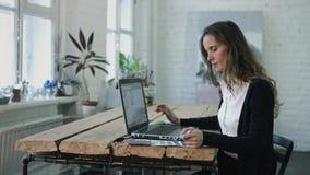 La mujer que trabaja por el ordenador portátil y que elige color metrajes