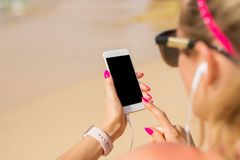 La mujer que usa el teléfono móvil y escucha la música al aire libre fotos de archivo
