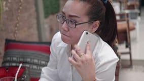La mujer que usa smartphone y las bebidas riegan de una taza de cristal despu?s de una comida almacen de metraje de vídeo