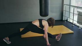 La mujer que va para los deportes en el centro de aptitud se sienta en las fracturas longitudinales metrajes