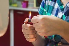 La mujer quema la tela roja por la llama del lighte foto de archivo