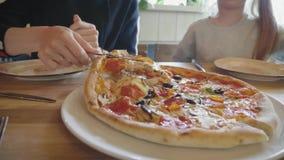 La mujer quiere tomar la rebanada de pizza caliente en el restaurante Familia que come la pizza italiana real y que se divierte F almacen de metraje de vídeo