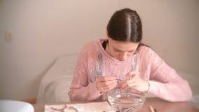 La mujer quita la cutícula con el empujador Hace la manicura misma Herramientas de la manicura en la tabla metrajes
