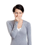La mujer ríe nerviosamente cubierta su boca Fotografía de archivo