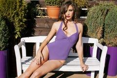 La mujer real joven de la belleza después del balneario en bikini y el traje en el hotel recurren, en terraza gozando del sol cal Foto de archivo libre de regalías