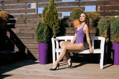 La mujer real joven de la belleza después del balneario en bikini y el traje en el hotel recurren, en terraza gozando del sol cal Fotografía de archivo libre de regalías