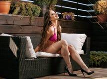 La mujer real joven de la belleza después del balneario en bikini y el traje en el hotel recurren, en terraza gozando del sol cal Imágenes de archivo libres de regalías