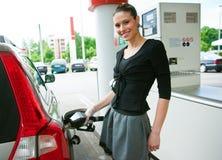 La mujer reaprovisiona su coche de combustible Fotografía de archivo