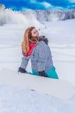 La mujer rechoncha joven con una snowboard en el esquí se inclina, arrodillándose en la nieve Foto de archivo