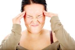 La mujer rechoncha tiene dolor de cabeza Fotografía de archivo libre de regalías