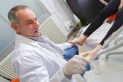 La mujer recibe el examen del pie de podiatra con guantes Foto de archivo libre de regalías