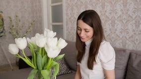 La mujer recibe las flores con el mensaje