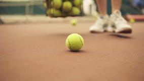 La mujer recoge las pelotas de tenis en el piso en la corte metrajes