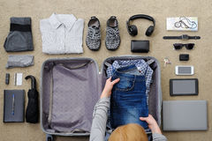 La mujer recoge una maleta para el viaje y el ocio Imágenes de archivo libres de regalías