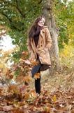 La mujer recorre en hojas de otoño Fotos de archivo libres de regalías