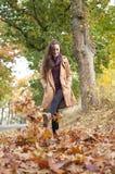 La mujer recorre en hojas de otoño Imagen de archivo libre de regalías