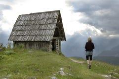 La mujer recorre a la cabaña abandonada de la montaña Foto de archivo libre de regalías