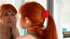 La mujer Redheaded saca maquillaje antes del espejo almacen de metraje de vídeo