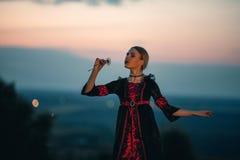 La mujer reflexiona sobre el fondo del cielo de la puesta del sol Fotos de archivo libres de regalías
