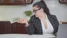La mujer regordeta confiada joven que trabaja con el ordenador portátil que da el dinero a una persona irreconocible, pero a nadi almacen de metraje de vídeo