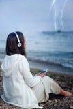 La mujer relaja música que escucha debajo de la lluvia, sentándose en una playa del mar Imagen de archivo libre de regalías