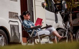 La mujer relaja y lee un libro cerca de acampar fotos de archivo libres de regalías