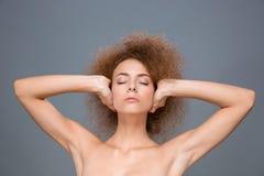 La mujer relajada joven con los ojos cerró los oídos de la cubierta por las manos Imagen de archivo libre de regalías
