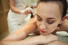 La mujer relajada que tiene máscara del cuerpo de la arcilla se aplica por el cosmetólogo Foto de archivo