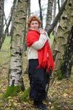 La mujer reservada de los años medios en un rojo robó costes entre abedules en la madera Imágenes de archivo libres de regalías