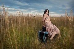 La mujer retra se está sentando en el campo foto de archivo