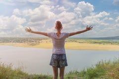La mujer retrocede con los brazos abiertos La vista del río y de la colina Cielo azul con las nubes fulgor imagen de archivo