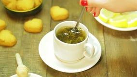 La mujer revuelve adentro la cuchara en la taza blanca en la tabla de madera Recientemente té de verde almacen de metraje de vídeo