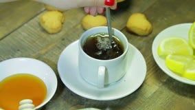 La mujer revuelve adentro la cuchara en la taza blanca en la tabla de madera Té negro recientemente preparado metrajes