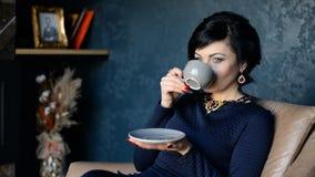La mujer rica hermosa bebe el café mientras que se sienta en una silla almacen de metraje de vídeo