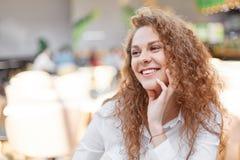 La mujer rizada alegre tiene sonrisa agradable, mira con la expresión feliz lejos, siente relajada y encantado, lleva la blusa bl Imagenes de archivo