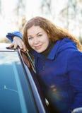 Muchacha rizada en capa azul con el coche que mira la cámara Fotos de archivo