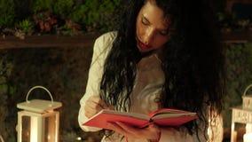 La mujer rizada joven toma notas almacen de video