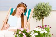 La mujer roja del pelo de la terraza del verano se relaja en deckchair Imagen de archivo