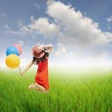 La mujer roja feliz que salta y que sostiene los globos en arroz verde coloca Imagen de archivo