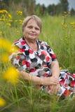 La mujer romántica del pensionista se relaja en hierba Fotos de archivo