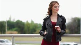 La mujer romántica en una chaqueta de cuero y con un café en sus manos mira lejos metrajes