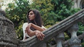 La mujer romántica es barandillas de piedra cercanas derechas en un jardín en día almacen de metraje de vídeo